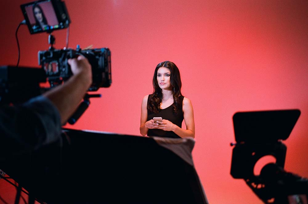 Model against a vivid, color backdrop in the video studio